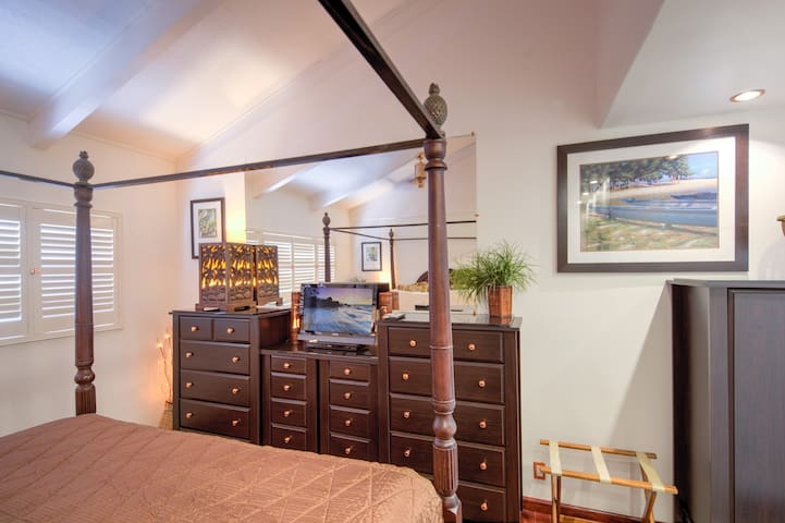 Bedroom with sets of dressers, armoire, flat screen TV, Blu-ray DVD player, carved palm tree lamps, and fun lighting