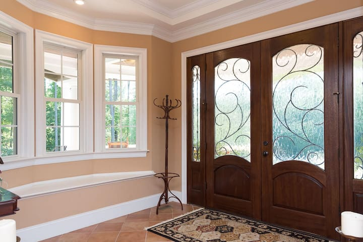 Solid mahogany double doors with graceful iron touches and rippled glass, a sitting area and a rustic mexican tile welcome you to the home.