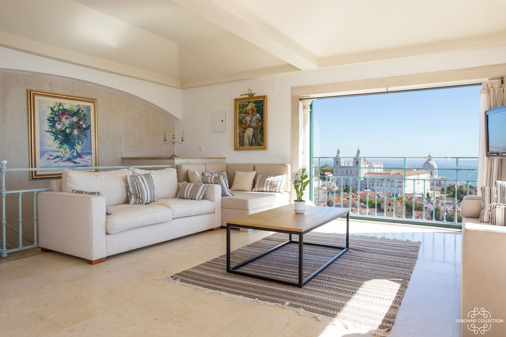 Living room with big sofa with view over the city and Tagus river.