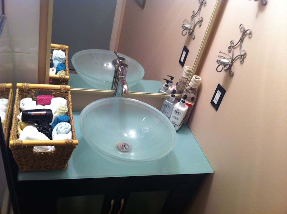 Elegant washbasin in bathroom, complete with glass-enclosed shower with variable massage hand held shower head.