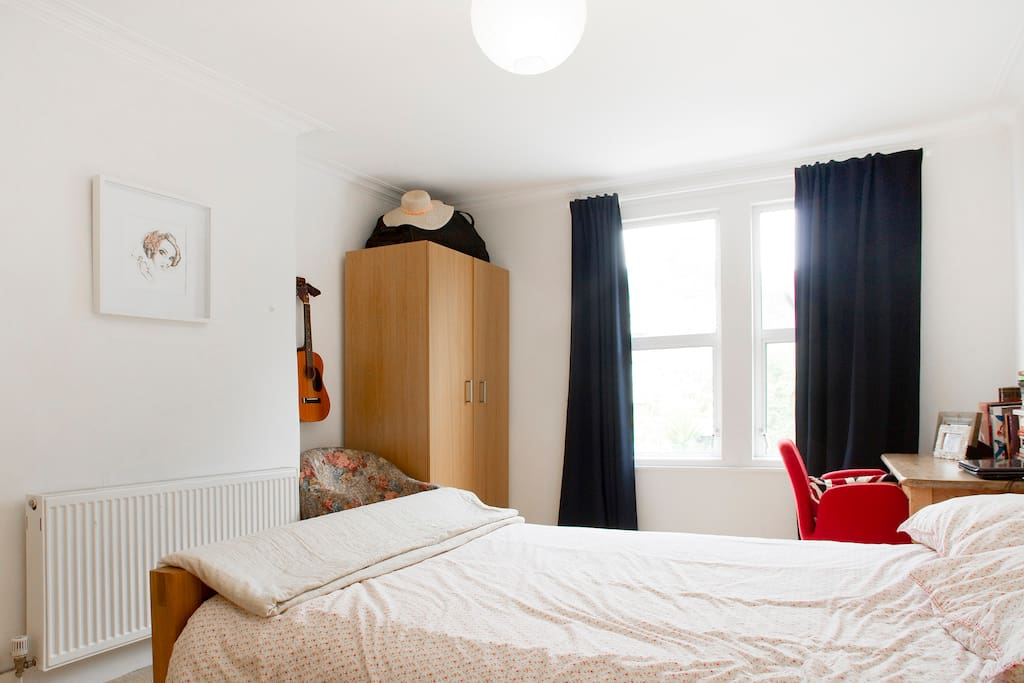 The bedroom includes ample storage space and big bright windows overlooking a back garden