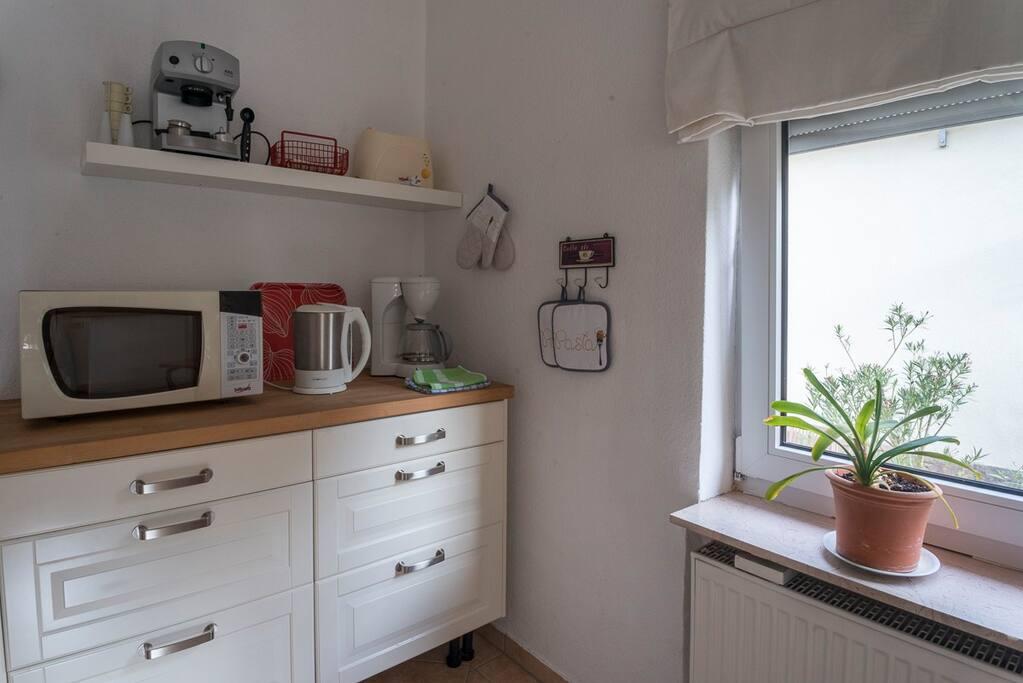 Wohnküche mit Kaffeemaschine, Teekocher, Mikrowelle, Espressomaschien, Toaster, Kühlschrank, Herd und Spüle.