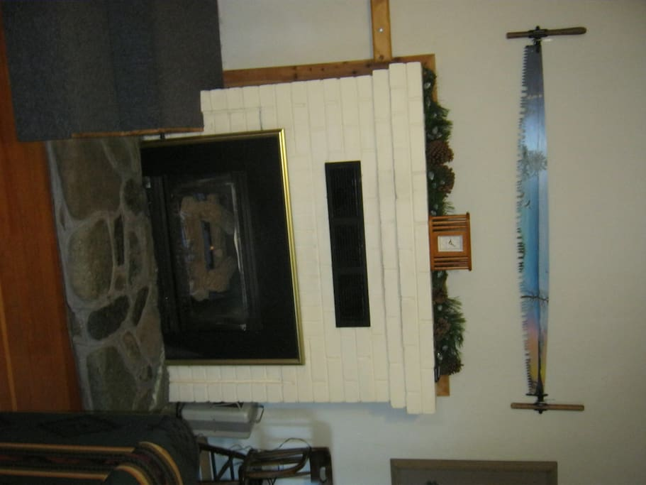 "Tilt your head to see the brick gas log fireplace with river rock hearth.  Custom painted ""4 seasons"" 2-man saw we originally found under the cabin."