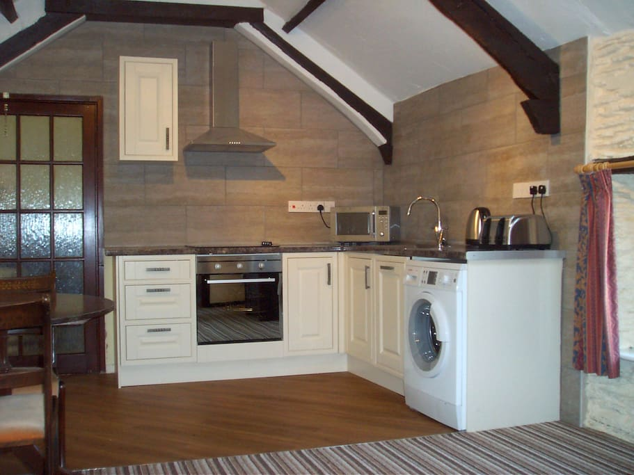 Fitted kitchen area with oven, microwave, fridge and washing machine.