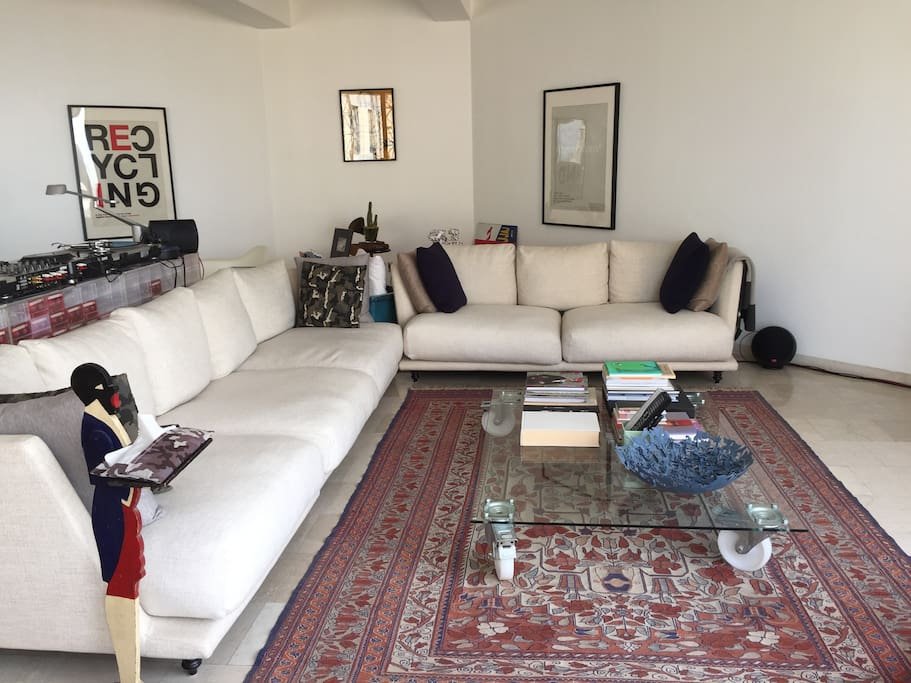 Main lounge area in living room with lots of natural light, large canvas sofa with pillows, seats 10+ ppl.