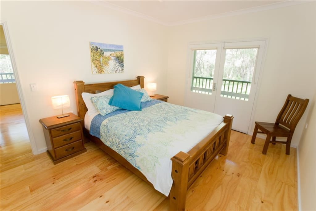 The main bedroom downstairs. A queen bed with its own French door to the verandah.