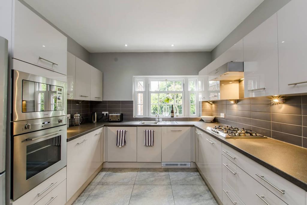 """Lovely oyster coloured glossy Italian Kitchen with integrated Dishwasher, Washing machine, separate Dryer, Microwave, oven, gas hob."" Simone, your host and awarded AIRBNB ""Superhost"" 2017"