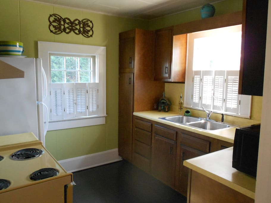 Watch the birds in the feeder below from the sunny kitchen, complete with appliances, dishes, glasses, utensils, coffee maker, microwave, toaster, and blender.