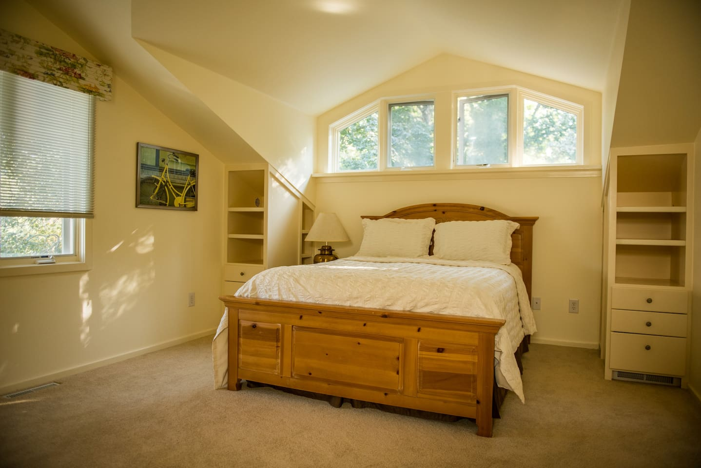 Spacious, light-filled bedroom with queen-sized bed,built-in shelves and desk.