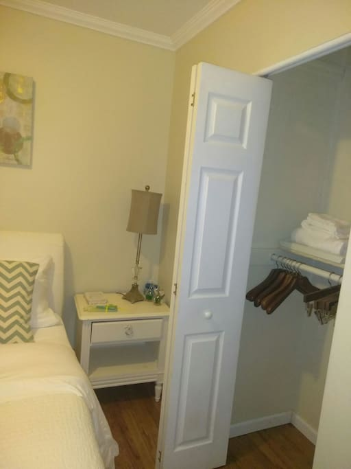 Cozy bedroom with full bed an arm chair and a closet with hangers. Also TV with internet access.