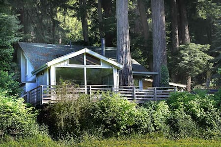 Amazingly Beautiful, Airy Riverfront Home with Modern Styling set in Magical, Tranquil Grove of Redwood Trees, Woodstove, Hot Tub, Lawn, Seasonal River Access and Boats, WIFI, Keyless Entry. Short Drive to the Coast, Duncans Mills, and Redwoods.