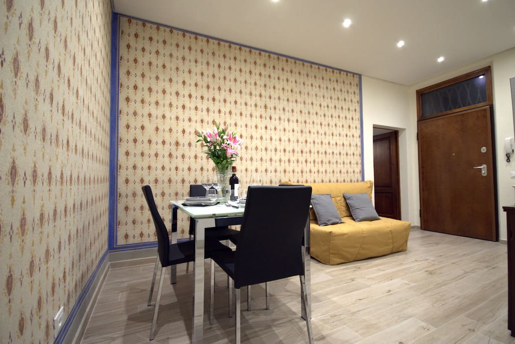 Living area with table, chairs, Tv, Double sofabed, original hand decorated wall, Air Conditioning, full equipped Kitchen