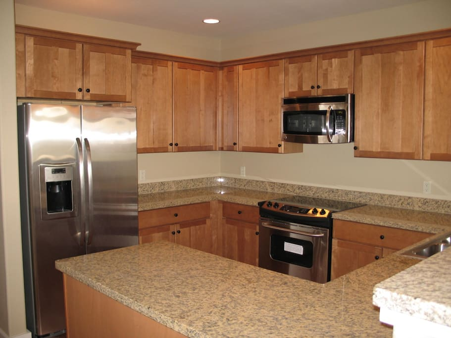 Kitchen with granite countertops & stainless steel appliances.