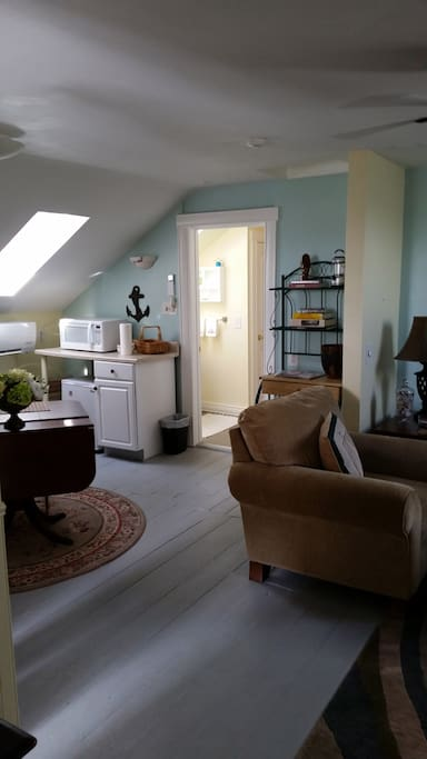 Kitchenette offers microwave, small refrigerator, and counter space with food storage rack.