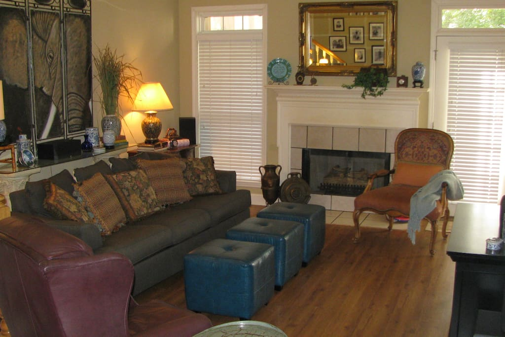 Spacious living room with gas logs overlooks deck and wooded back yard