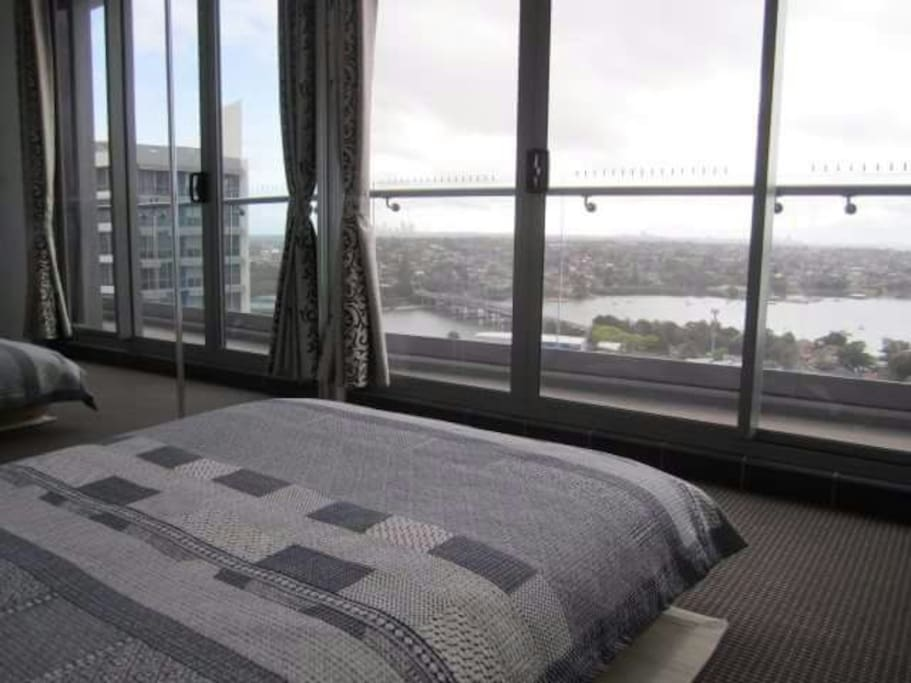 Guest bedroom with Japanese style futon bed (double size) and mirrored built in wardrobe. Access to balcony with harbour and city views.