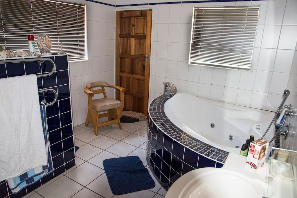 Full ensuite bathroom with spa bath, toilet and shower