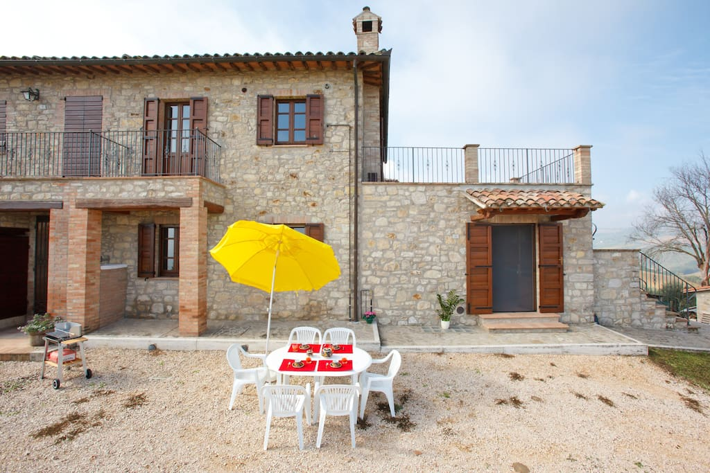 Esterno della casa con barbecue, tavolo, sedie e ombrellone