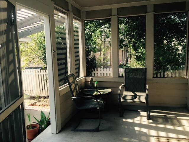 Screened in back porch, with a ceiling fan.