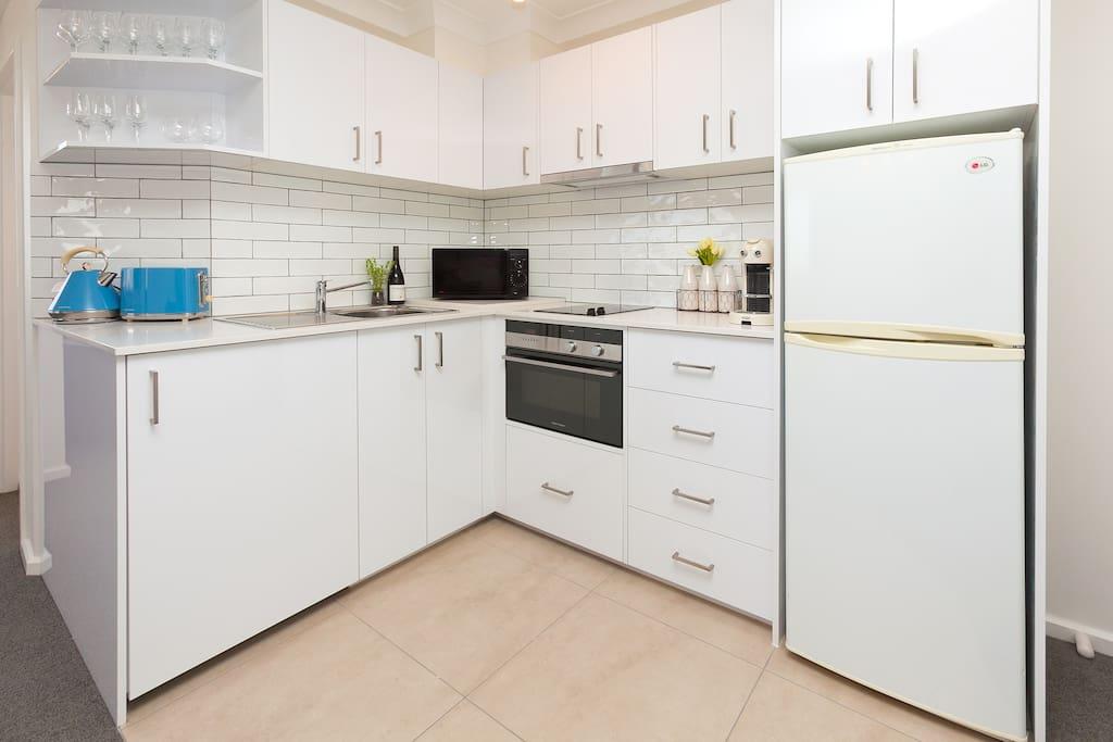 Full sized kitchen with European appliances.