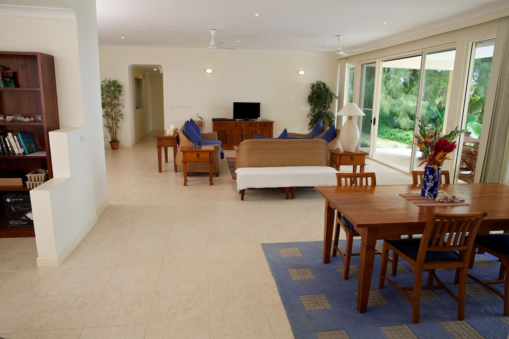 Large living/dining area with floor to ceiling windows looking out over the ocean.