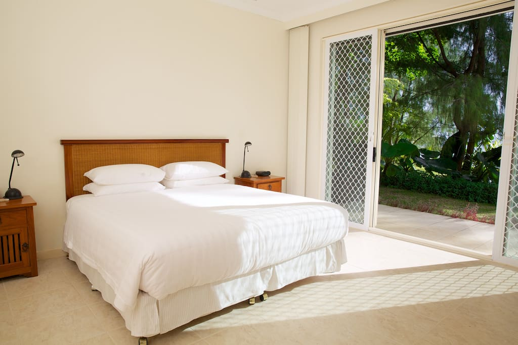 Large main bedroom with super comfy king size bed and floor to ceiling windows with a view of the ocean.