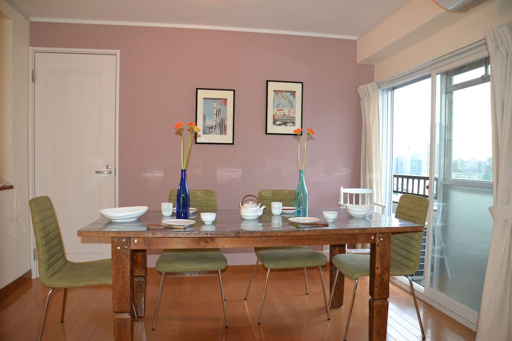 Dining room with an antique teak table, 6 chairs and plenty of utensils.