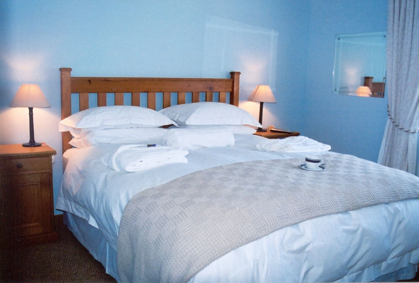 This room has a queen size bed and full en suite bathroom. The light blue walls and straw-coloured carpeting provide a warm atmosphere.