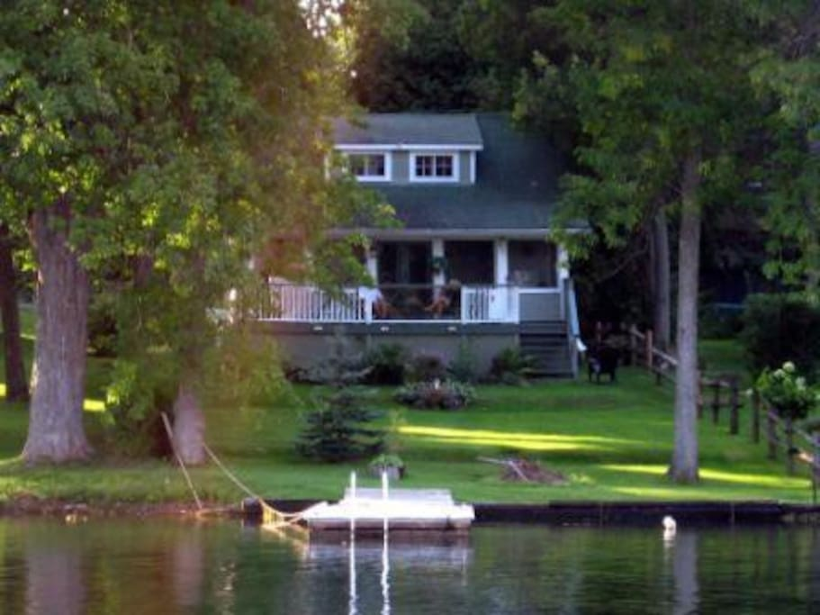 Riverside view of cottage showing dock, lawn, deck and screened porch from across river.