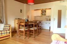 Le salon avec parquet et cuisine aménagée.