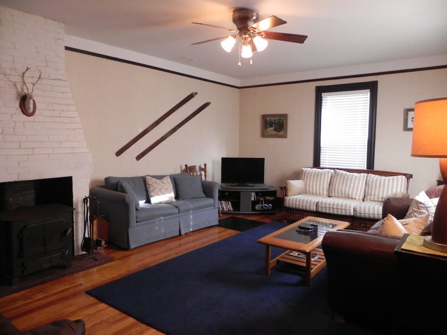 First Living room adjacent to kitchen.  Woodstove, plasma TV with cable, Wii, and pull out couch. Seats 10.