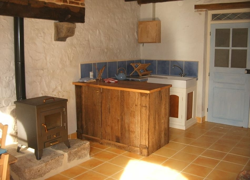 Kitchen area with a gas cooker & oven, fridge & sink.