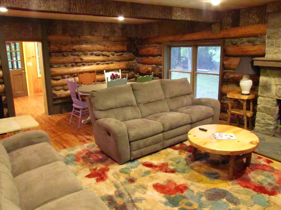 This is the main living area with gas logs, Roku TV, dining for six people. There is a 1/2 bath and daybed to the left. The doorway in the top left leads to the kitchen and screened porch.