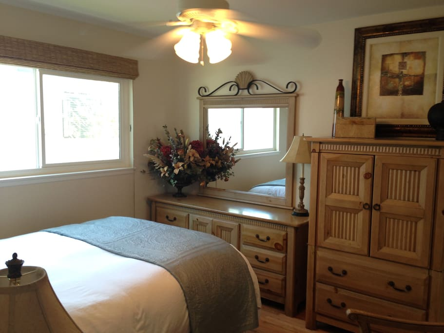 Guest room with queen bed and television inside the armoire.