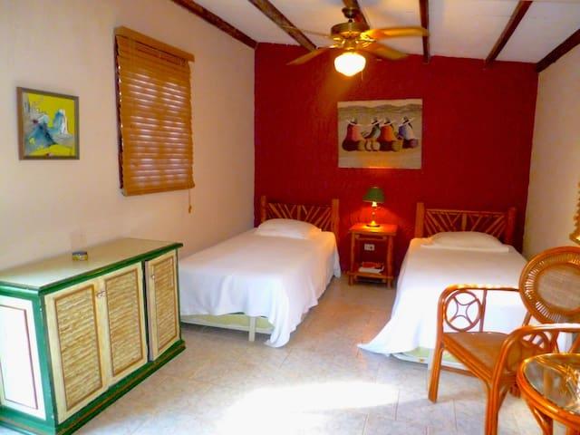 Casita de huéspedes con dos camas individuales y dos camas de piso.