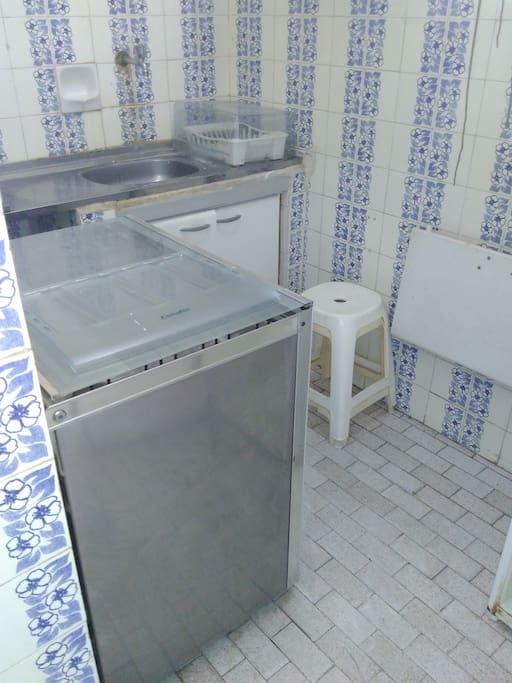 Cozinha aparelhada, fogão, pequena mesa, geladeira.