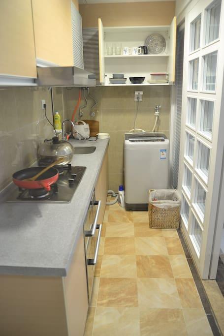 Kitchen with washing machine and kitchenware
