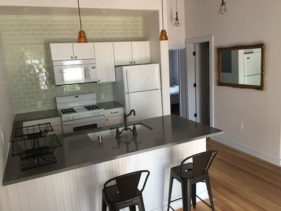 Brand new kitchen with quartz counters and an eating area for two.
