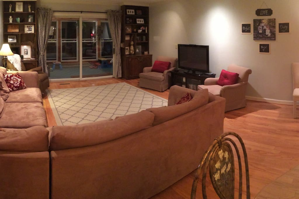 Large living room/dinning room with oversized sectional couch, leading out to heated sunroom.