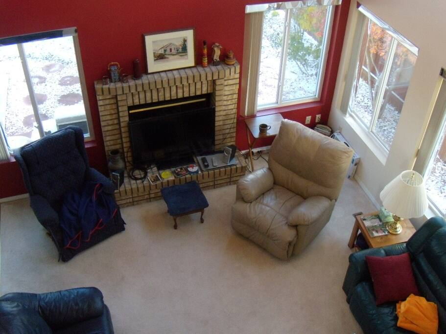 The gathering room, aka den, with 3 couches, two recliners, fireplace, flat screen tv, and seven large windows to enjoy Colorado sunshine and scenery