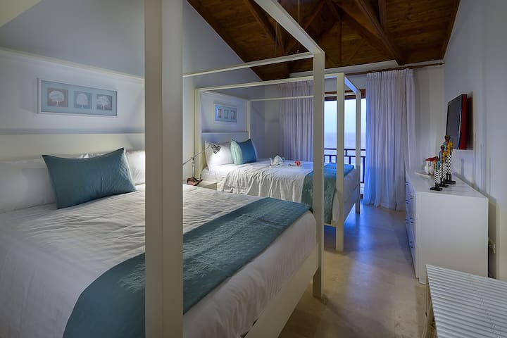 This light-filled stately bedroom has two luxurious queen size beds, en suite bathroom, a television with cable, and a balcony with an ample view of the deep blue sea