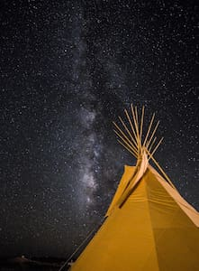 Large, simple tipi with gravel floor, a full bed, electricity, wifi and a table and chairs to enjoy the surroundings. You have your own private bathroom located just outside. It is located in the ghostown within walking distance of every restaurant.