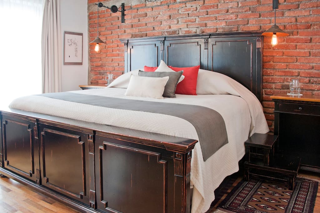 Industrial design with vintage strokes and two steps in wood each side to get up on the bed