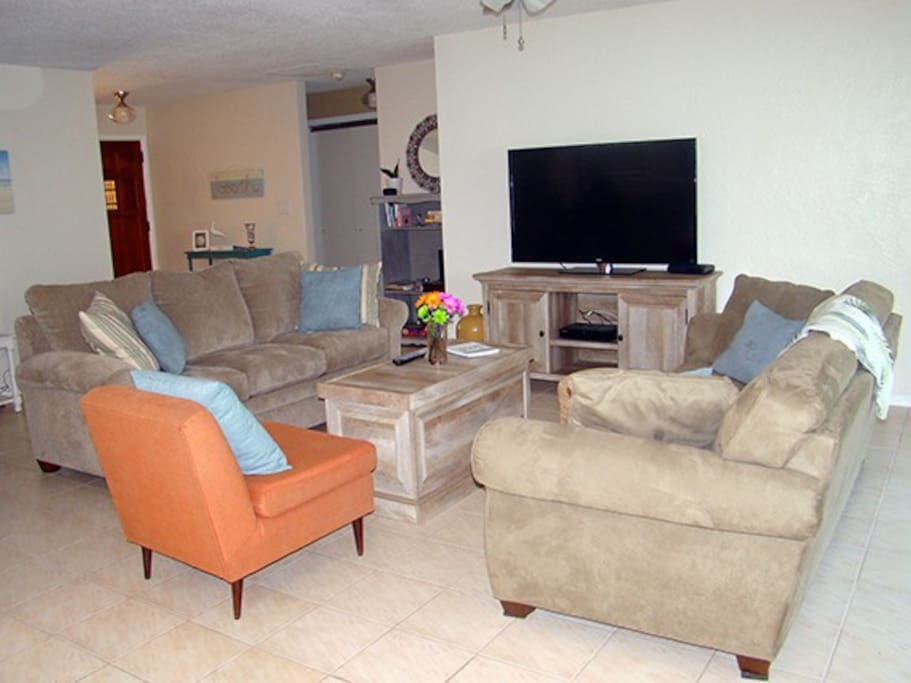"""Spacious living room with queen size sofa bed and 55"""" TV"""