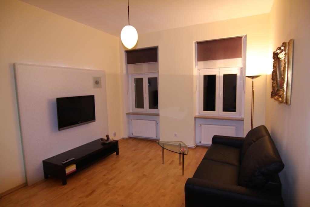 Wohnzimmer der Ferienwohnung Berlin bei Nacht. Blick zum Fernseher