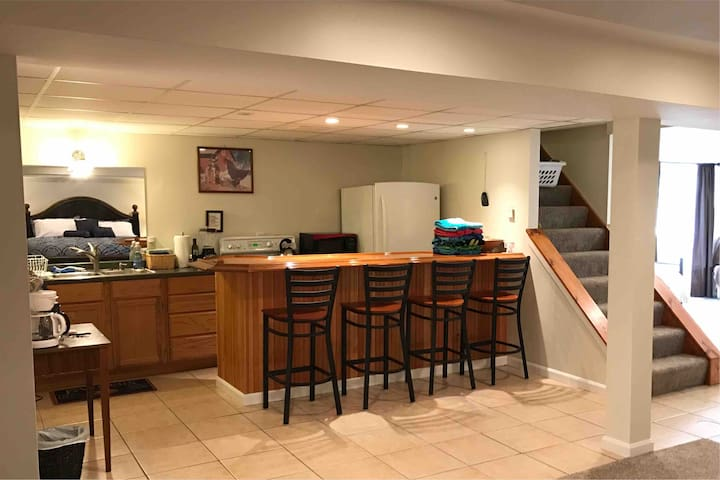 View of kitchenette/bar across from the master bedroom area (see in mirror over sink) with view to first bedroom area with full size bed! Full-size appliances for your convenience.