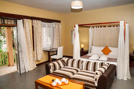 A spacious King suite with quality Hotel bed linen, sitting area with TV kitchenette and balcony.