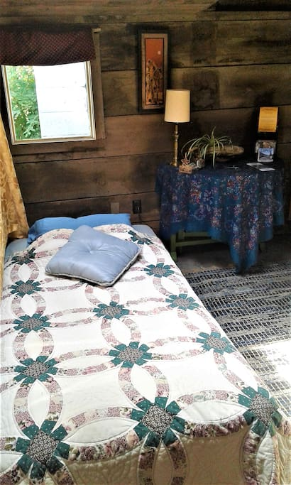 Twin bed in entry bedroom.  There is also a table and chair.