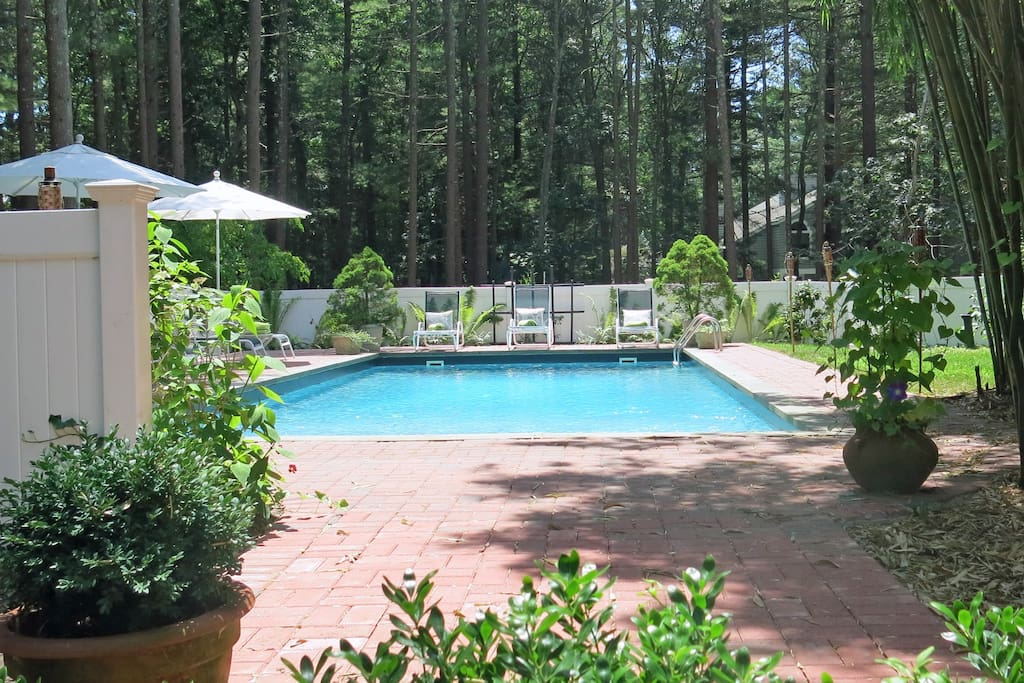 A bluestone terrace at the back of the house leads to a brick walkway and then the heated pool.