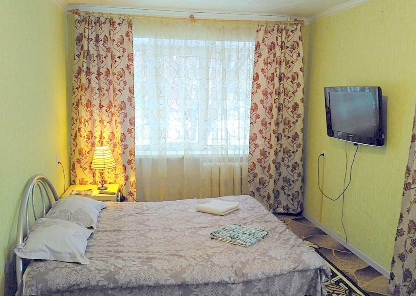 Кровать с телевизором в комнате